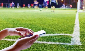 Fußball Sportwetten mit Handy am Spielfeld